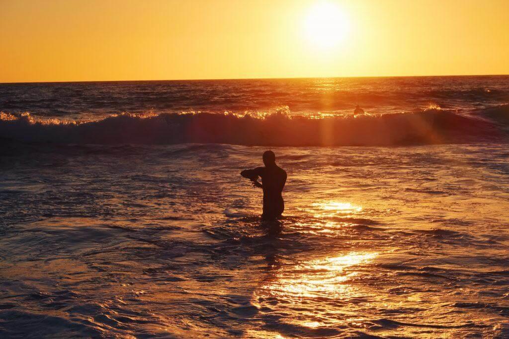 Mensch im Meer bei Sonnenuntergang